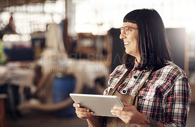 Buy stock photo Cropped shot of an attractive young woman looking thoughtful while working on her tablet in her creative workshop
