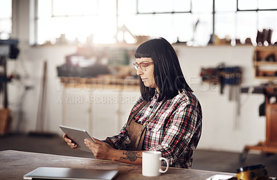 Buy stock photo Cropped shot of an attractive young woman working on her tablet while sitting in her creative workshop