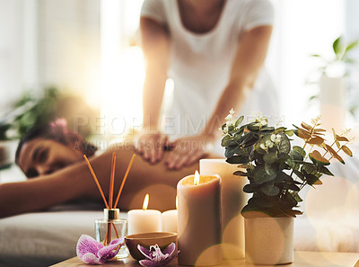 Buy stock photo Shot of spa essentials on a table with a woman getting a massage in the background