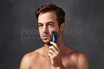 Buy stock photo Cropped shot of a handsome young man shaving against a grey background
