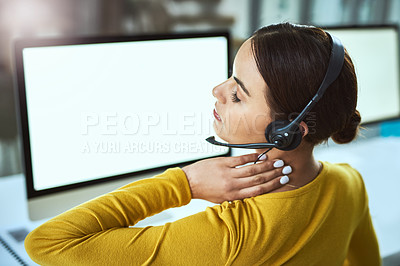 Buy stock photo Rearview shot of a call centre agent suffering with neck pain while working in an office