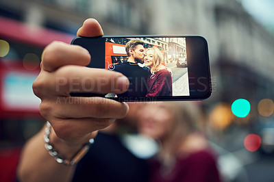 Buy stock photo Shot of a happy young couple taking a selfie with a mobile phone in the city