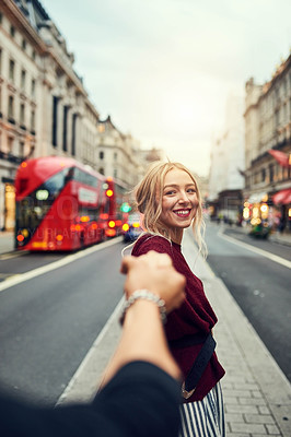 Buy stock photo Shot of a young woman holding her boyfriend's hand while out in the city