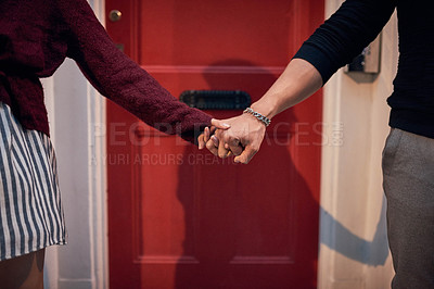 Buy stock photo Cropped shot of an affectionate young couple holding hands in the city