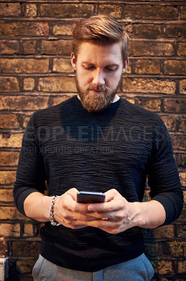 Buy stock photo Shot of a young man using a smartphone against a brick wall in the city