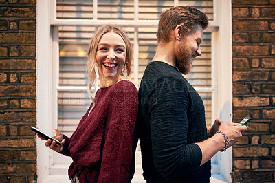 Buy stock photo Shot of a young man and woman standing back to back and using their smartphones