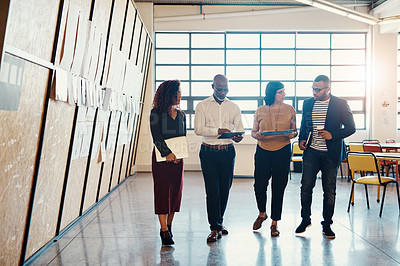 Buy stock photo Shot of a group of designers having a discussion while walking through a office