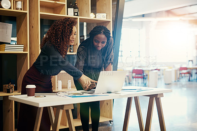 Buy stock photo Shot of two businesswomen discussing something on a laptop at the office