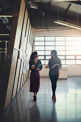Buy stock photo Shot of two businesswomen having a discussion while walking through a office