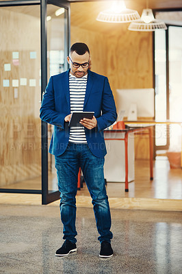 Buy stock photo Shot of a young businessman using a digital tablet at the office
