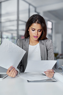 Buy stock photo Cropped shot of a young businesswoman looking through some paperwork in an office