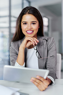 Buy stock photo Cropped portrait of a young businesswoman working on a digital tablet in an office