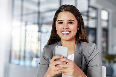 Buy stock photo Cropped portrait of a young businesswoman texting on a cellphone in an office