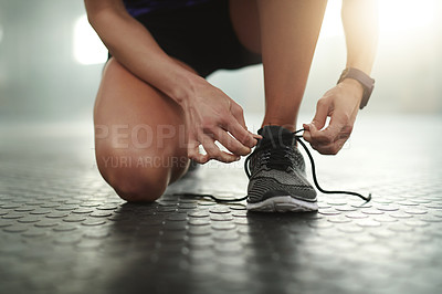 Buy stock photo Cropped shot of an unrecognizable woman tying her shoelaces in the gym