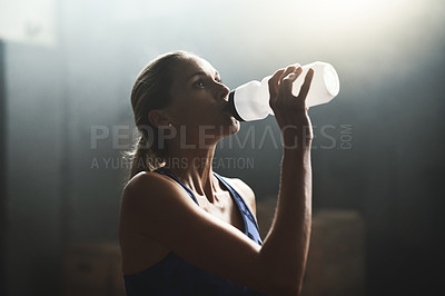 Buy stock photo Cropped shot of an athletic young woman drinking water in the gym