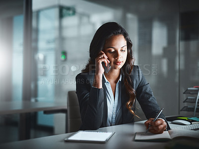 Buy stock photo Shot of a young businesswoman using a mobile phone while working late in a modern office