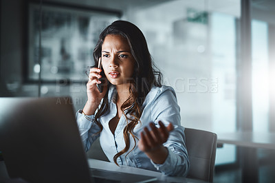 Buy stock photo Shot of a young businesswoman using a mobile phone and laptop while working late in a modern office