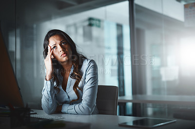 Buy stock photo Shot of a young businesswoman looking stressed out while working late in a modern office