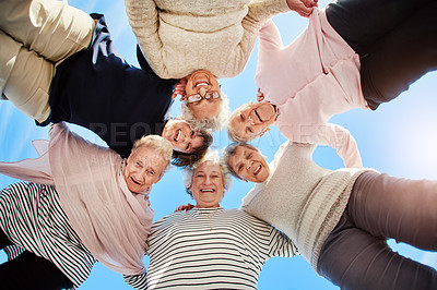Buy stock photo Low angle portrait of a group of happy senior women huddled together together outdoors