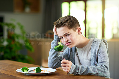 Buy stock photo Cropped shot of a teenage boy refusing to eat his vegetables at home