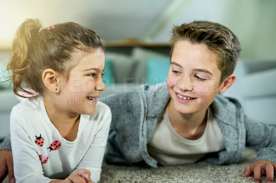 Buy stock photo Cropped shot of two loving siblings lying on the floor together