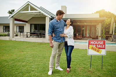 Buy stock photo Shot of a couple standing next to a real estate sold sign at their new house