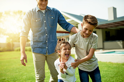 Buy stock photo Shot of a little girl laughing while outside with her brother and father