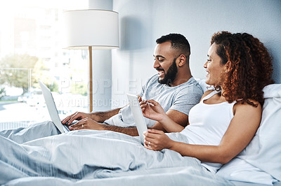 Buy stock photo Cropped shot of a young couple using their wireless devices while lying next to one another in their bed