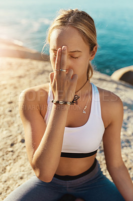 Buy stock photo Shot of a young woman doing yoga at the beach