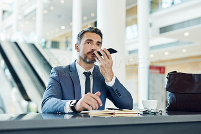 Buy stock photo Shot of a mature businessman using a mobile phone while sitting in an airport cafe