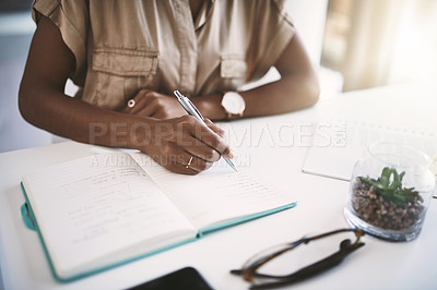 Buy stock photo Shot of a young businesswoman writing notes at her desk in a modern office