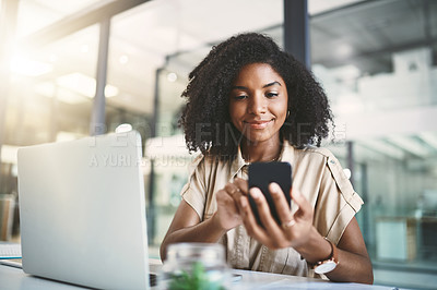 Buy stock photo Shot of a young businesswoman using a mobile phone and laptop at her desk in a modern office