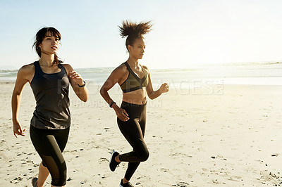 Buy stock photo Cropped shot of two attractive and athletic young women out for a run on the beach