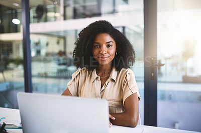 Buy stock photo Portrait of a young businesswoman using a laptop at her desk in a modern office