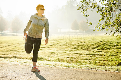 Buy stock photo Full length shot of an attractive mature sportswoman stretching before her early morning run in the park