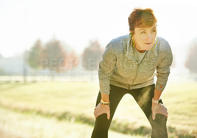 Buy stock photo Cropped shot of an attractive mature sportswoman looking tired while taking a break from her early morning run in the park