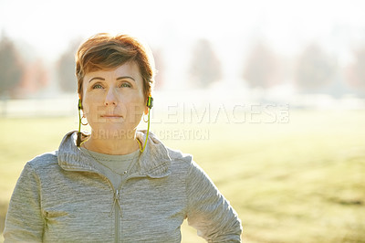 Buy stock photo Cropped shot of an attractive mature sportswoman standing in the park during an early morning workout