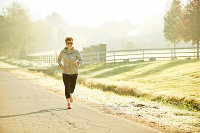 Buy stock photo Full length shot of an attractive mature sportswoman out for an early morning run in the park