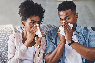 Buy stock photo Shot of a young couple blowing their noses on the sofa at home