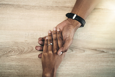 Buy stock photo Cropped high angle shot of a man and woman holding hands at a table