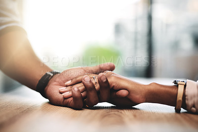Buy stock photo Cropped shot of a man and woman holding hands at a table