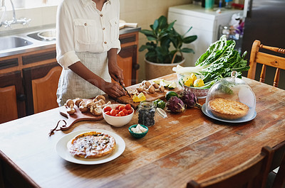 Buy stock photo Cropped shot of a woman preparing a healthy meal in the kitchen at home