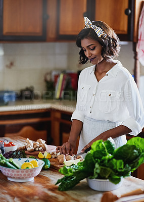 Buy stock photo Shot of a young woman preparing a healthy meal in the kitchen at home