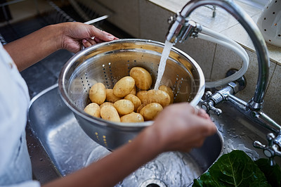 Buy stock photo Cropped shot of a woman rinsing potatoes in a kitchen sink at home