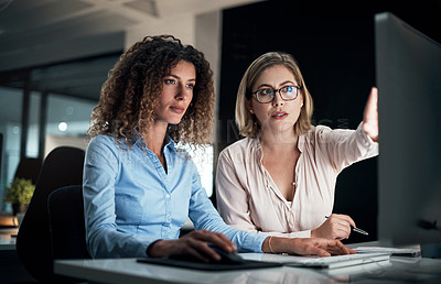 Buy stock photo Cropped shot of two attractive young businesswomen working late at the office