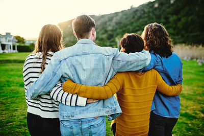 Buy stock photo Rearview shot of a group of friends arms around each other outdoors