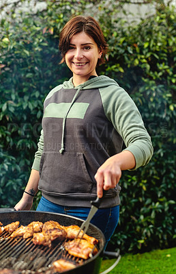 Buy stock photo Cropped shot of a young woman tending to the barbecue outdoors