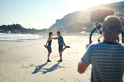 Buy stock photo Rearview shot of a focused young man shooting a scene with a state of the art video camera outside on a beach during the day