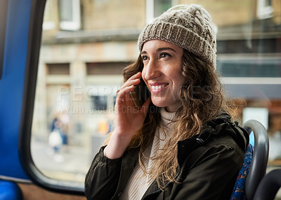 Buy stock photo Shot of a young woman using a mobile phone while traveling on a bus