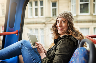 Buy stock photo Shot of a young woman using a digital tablet while traveling on a bus